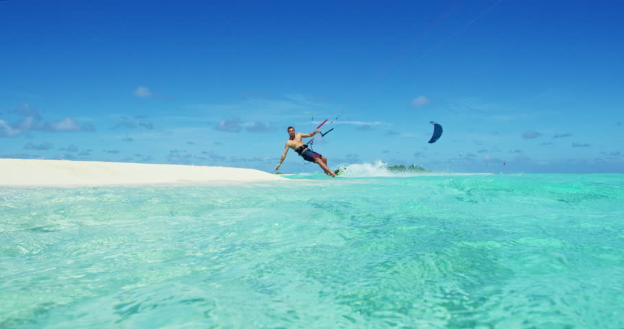 Young man kitesurfing in tropical blue ocean