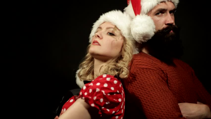 blond and bearded brunette in caps of Santa Claus standing next to a black background