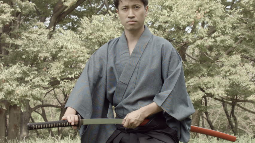 Japanese Samurai draws his sword called Katana, and slashes with it, resheaths it, over and over
