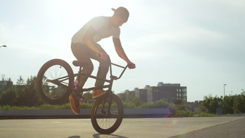 SLOW MOTION CLOSE UP: Extreme bmx biker riding in sunny park, stopping the bmx bike and doing nollie tail whip trick on beautiful summer day. Cool young bmx biker performing tricks on city street