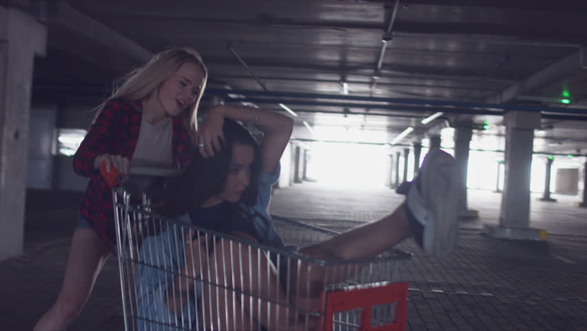 MED fashion funny young hipster girls having fun at the shopping mall parking, spinning each other in shopping cart. 60 FPS 4K UHD