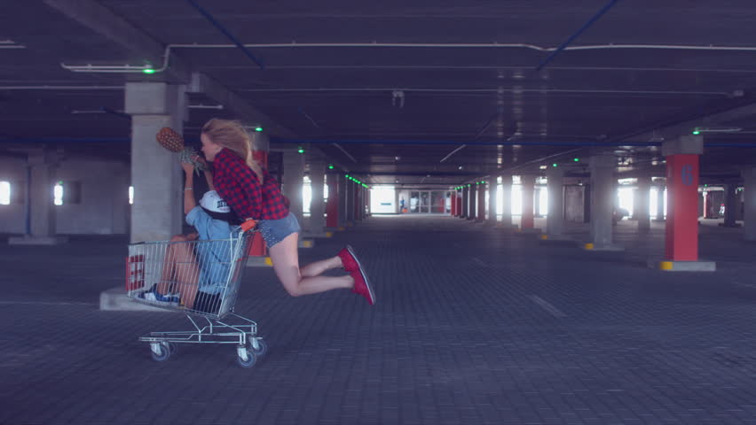 MED FOLLOW fashion funny young hipster teen girls having fun at the shopping mall parking, riding in shopping cart. 60 FPS 4K UHD
