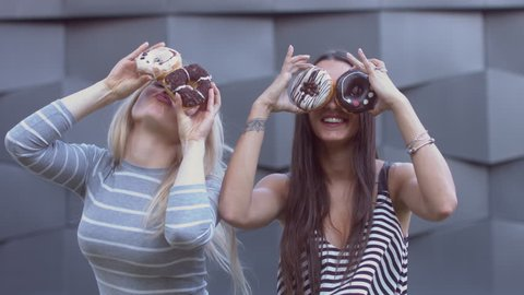 4K MED portrait of two young girls doing silly faces with donuts