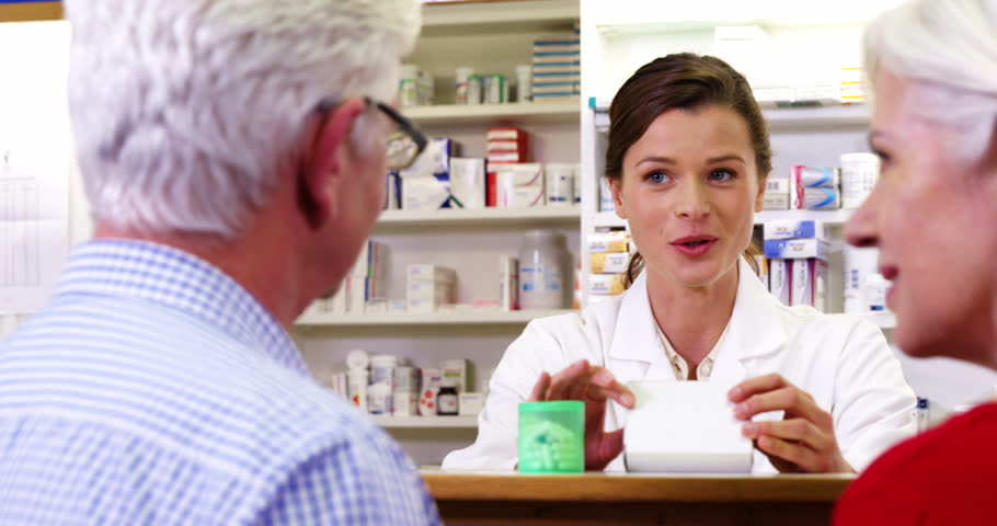 Pharmacist assisting the box of medicine to customers in pharmacy | Shutterstock HD Video #19686703