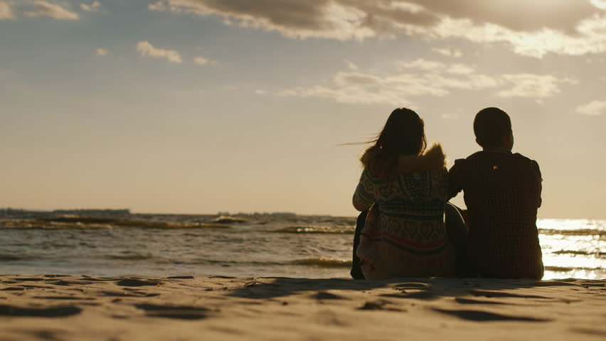 Loving couple sitting on the beach at sunset. Cool day, rear view | Shutterstock HD Video #19716292