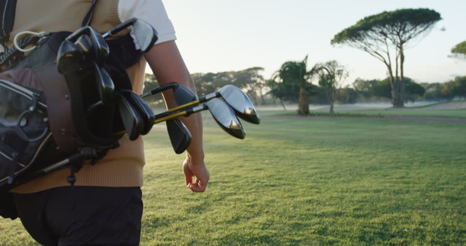 Golfer carrying his golf bag and walking on the golf course