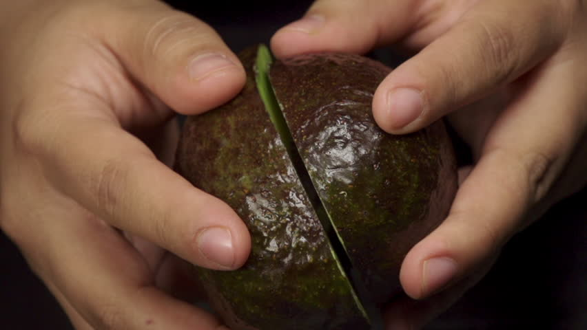 Table top shot of a chef opening an avocado in two parts