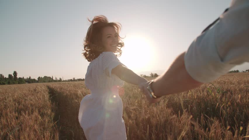 Follow me, young happy couple running through a field of Golden wheat at sunset, slow motion, lens flare