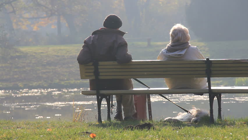 Elderly couple and a dog sitting quietly on park bench