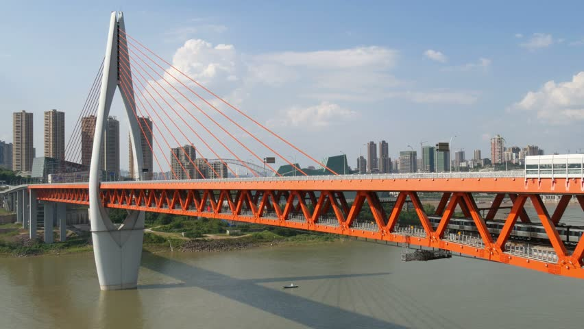 China Chongqing Qianximen twin river double deck bridge with train crossing moving away from view city skyline with tower blocks blue sky with clouds & Jialing river below #19805338
