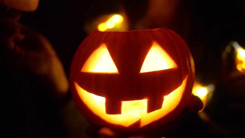 Halloween pumpkin with scary face with with a burning candle