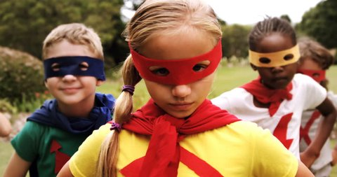 Portrait of group of kids pretending to be a super hero in the park 4k