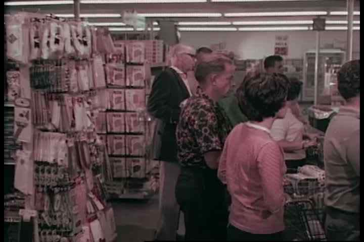 In a crowded supermarket, a love struck young couple walks down a grocery aisle, but they are arguing by the time their cart is full in the 1960s. (1960s)