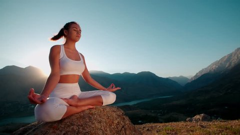 4K beautiful girl in Lotus white clothes doing yoga on the beautiful backdrop of the mountains,slow motion