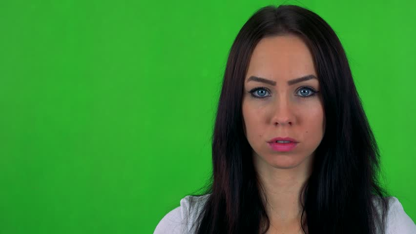 Young pretty woman looks to camera with serious face - green screen - studio  | Shutterstock HD Video #19831852