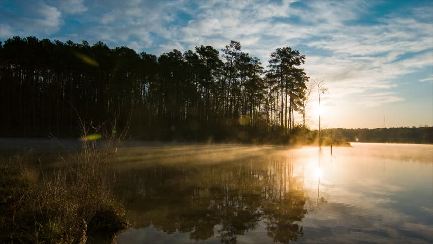 Morning Fog Moving Over the Water Surface of Lake Crabtree in Raleigh North Carolina in a Nature Scene with Golden Sunshine