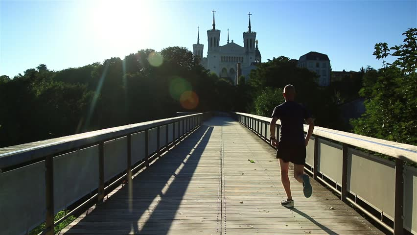 Man running over a footbridge on Fourviere hill, Lyon, just after sunrise.