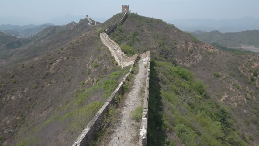 Drone flight over a beautiful quiet (partly decayed) stretch of the Great Wall of China, one of the most impressive human engineering projects of all times and an iconic landmark of imperial China