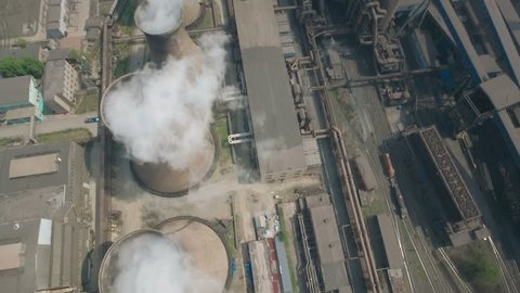 Overhead aerial view of coal fired reactors on the site of a large steel factory in Benxi, China. A cargo train carrying hot liquid steel rides along the railway tracks.a