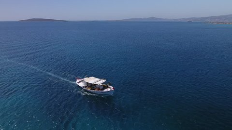 Aerial of a single Greek fishing boat on spectacular blue sea close to the island of Paros.