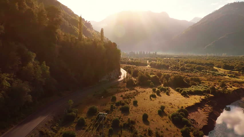 Aerial: Mountain road through valley at sunrise with car pickup truck driving