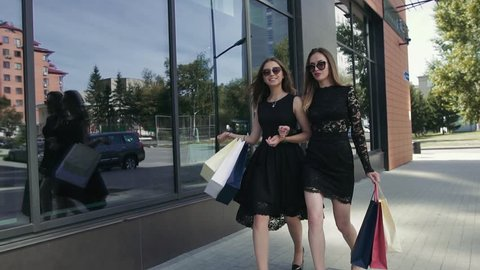 Two beautiful female friends walking after shopping