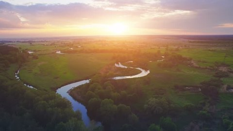 Aerial View: Flight over the Beautiful River and Green Wood. Sunset soft light with pastel cloudy sky. Magestic landscape. 4K resolution.