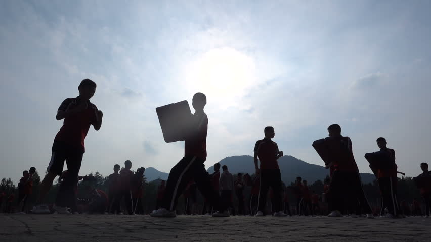 Slow motion of martial arts students practicing boxing skills at the playground of a major kung fu institute in Shaolin, the 'birthplace of kung fu', in central China