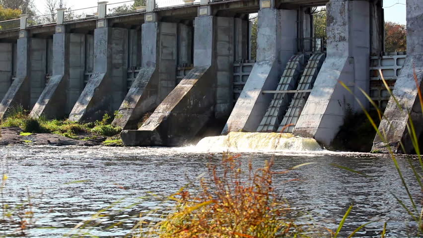 Dam with current water and red bushes in the foreground
