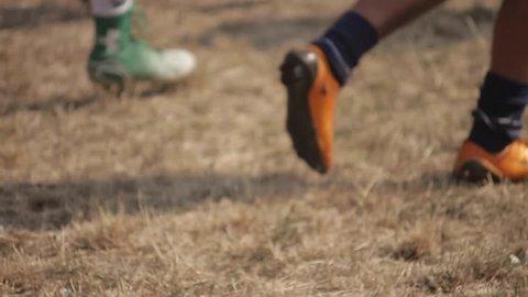 American football training. Men running on a football field. Legs and sportswear. Close-up.