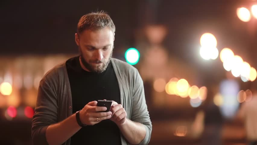 Handsome man texts, uses his smartphone and goes away. Blurred city lights in the street. Modern technology   Shutterstock HD Video #19931812