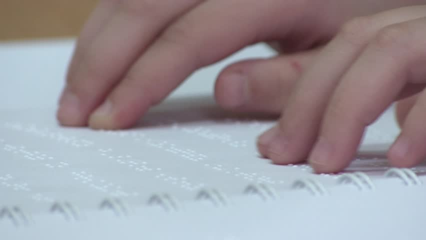 Reading Braille. The Child Learns to Read Braille on a sheet of paper sitting at the desk in the school