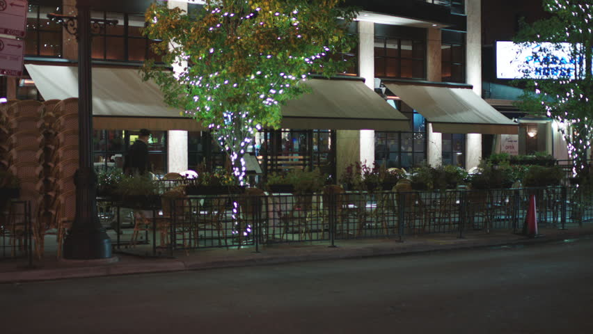 Night hold up angle tall apartments all glass front then tilt down 2 nice restaurants 2 story restaurant bar right, modern stone building, | Shutterstock HD Video #19953952