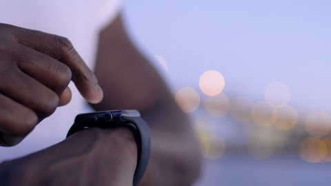Closeup Of Man using His Smartwatch With City Lights In Background