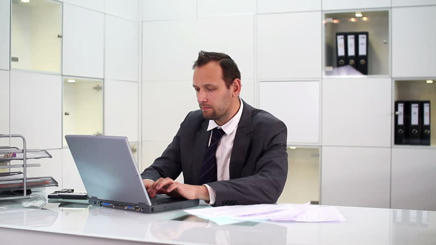 Angry businessman hitting and throw away laptop in the office