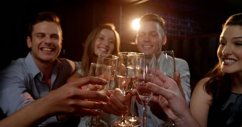 Group of smiling friends sitting on sofa and toasting a glasses of champagne at bar 4k