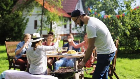 leisure, food and drinks, people and holidays concept - happy man grilling meat on barbecue party for his friends and drinking beer from bottle at summer garden