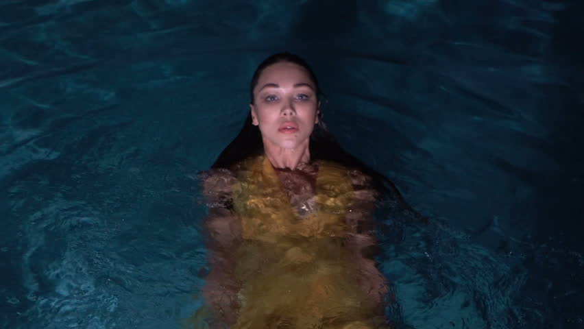155e47ed64a37 Gorgeous fashion woman with dark hair in elegant yellow dress looking into  the camera while standing in water of outdoor pool at night