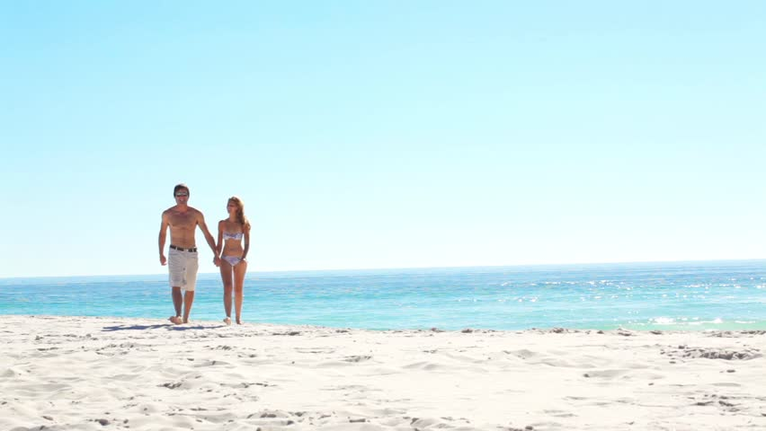 Romantic couple on honeymoon walk along a pristine beach in summer. gorgeous blue ocean and clear sky.