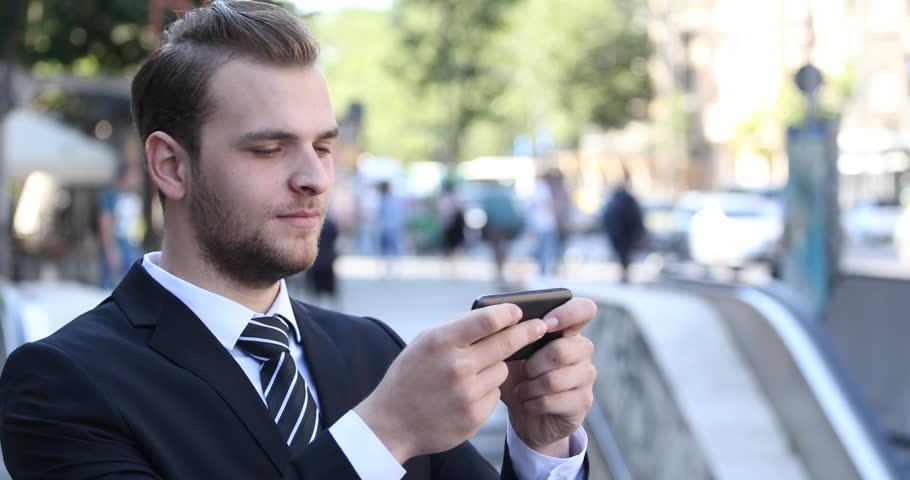 Businessman Portrait Sending Sms with Mobile Phone Texting Message City Center. Ultra High Definition, UltraHD, Ultra HD, UHD, 4K, 2160P, 4096x2160 | Shutterstock HD Video #20158522