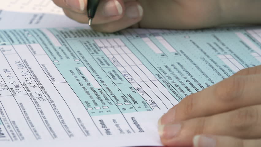 Fill in the form for taxes: US taxes, tax return, young woman | Shutterstock HD Video #20158702