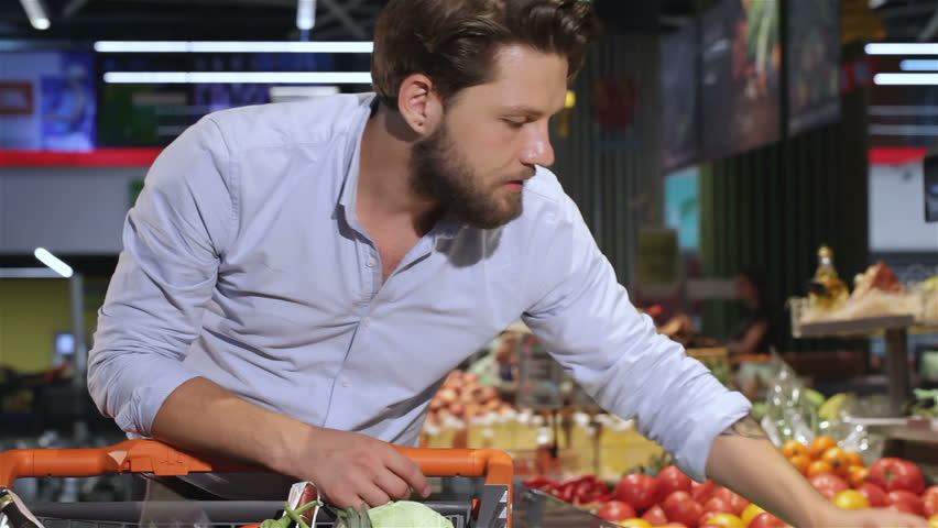 Stylish bearded man taking squashes from the tray at the supermarket. Young man looking at the squashes at the mall. Attractive brownhaired man smiling for the camera with zucchini in his hands