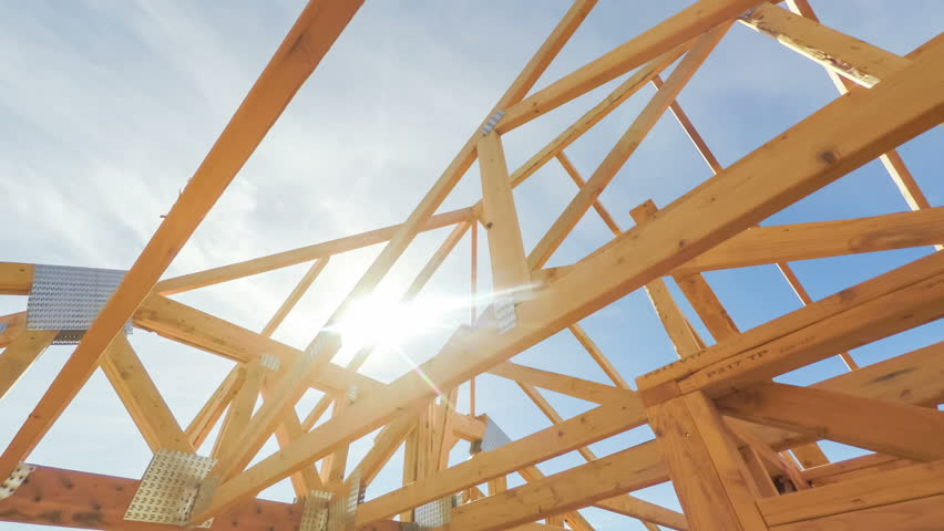 Roof Beams Of A Modern American Home In Mid Construction Phase, Looking Up  Toward Blue