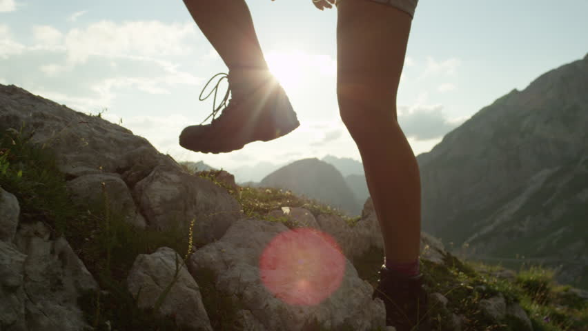 SLOW MOTION, CLOSE UP: Courageous female hiker climbing mountaintop, walking off trail on dangerous rough rocky mountain ledge. Steep wall opening beautiful view on high European Alps sunbathing
