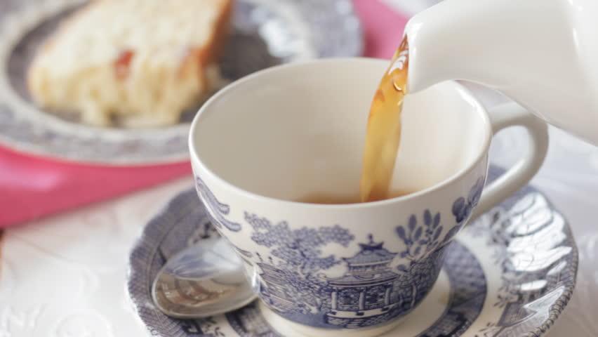 Pouring Tea Into An Antique Tea Cup, Lemons On The Side ...