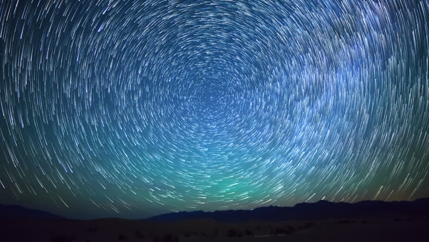 Astrophotography time lapse with pan left motion of star trails over sand dunes in Death Valley National Park, California