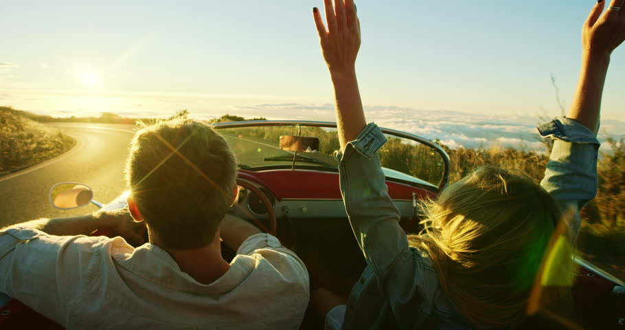 Happy couple driving on country road into the sunset in classic vintage sports car   Shutterstock HD Video #20219026