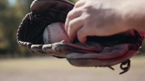 Slowmotion Close Up of Man Wearing Baseball Glove and Tossing Baseball from Hand to Hand During Baseball Game Outdoors in Field on Sunny Day in Summer.
