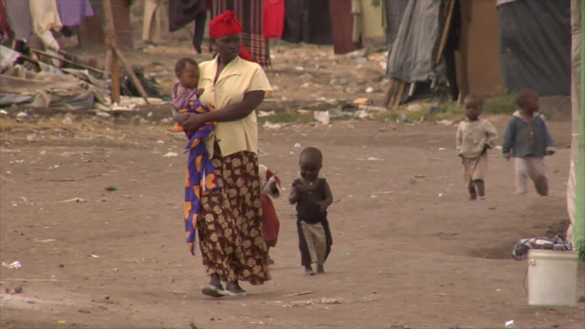 KENYA - CIRCA 2006: Unidentified African woman walks up a street followed by toddlers circa 2006 in Kenya.