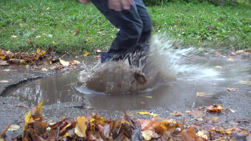 Boy jumping in muddy puddle, slow motion 250 fps #20244622